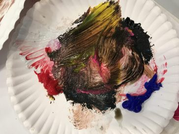 multiple colors of paint smeared on a plate