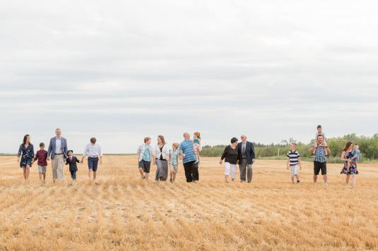 Extended family walking in harvested wheat field