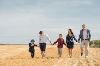 Family walking hand in hand in a harvested wheat field
