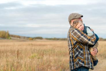 Father cuddling with son in field with wide open sky