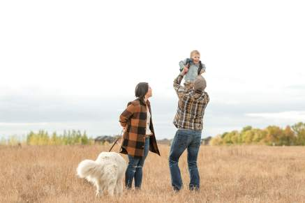 Father lifts his son up in the air during their family photography session