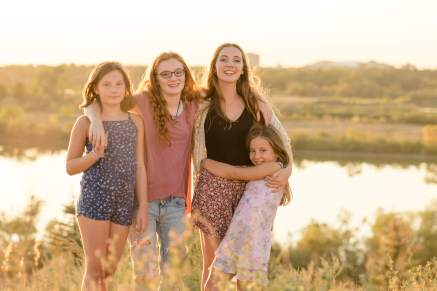 Four sisters hugging and smiling at sunset
