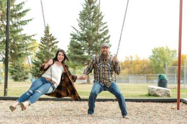 Husband and wife playing on the swings at the Lumsden campground