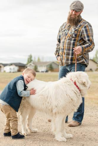 Little boy hugs his white dog Blanche Devereaux