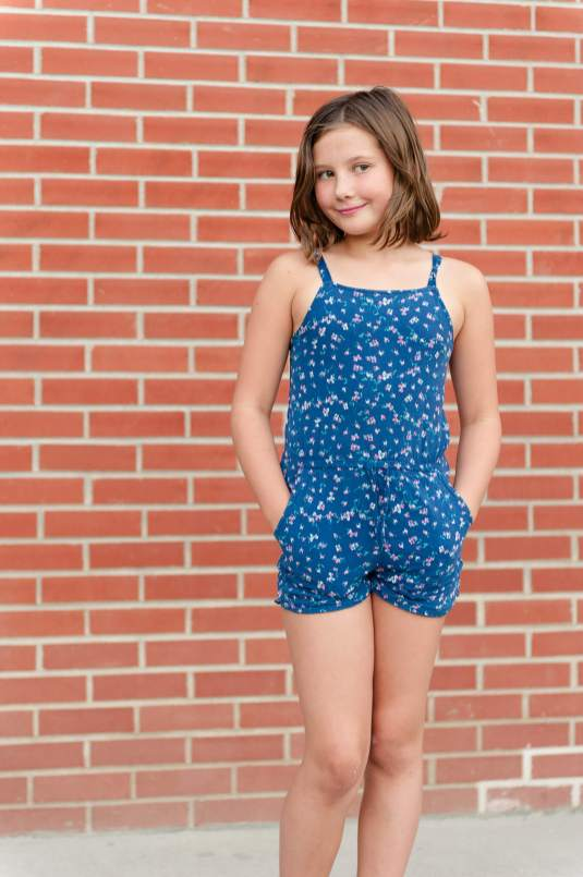 Little girl in romper standing in front of brick wall