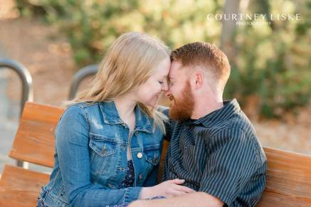 Blonde woman and red haired man sitting together on a park bench
