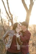 Couple kisses in the Lumsden Valley during their engagement shoot with Courtney Liske Photography