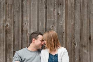 Couple resting their heads together in front of a wooden wall