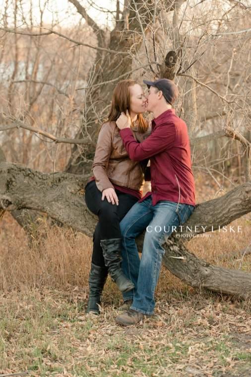 Couple sit on a broken down tree