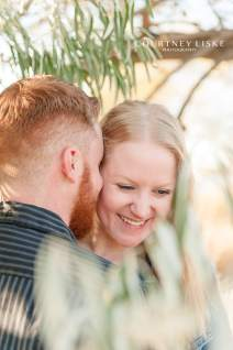 Engaged woman laughs with her fiancee under willow tree