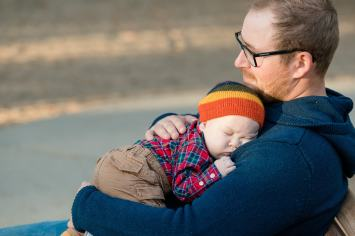 Father cuddles with sleeping baby boy on a bench in Wascana Park