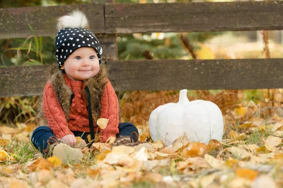 Little girl in beanie and vest sitting in leaves with white pumpkin