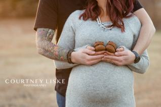 Couple hold hands and small brown baby shoes