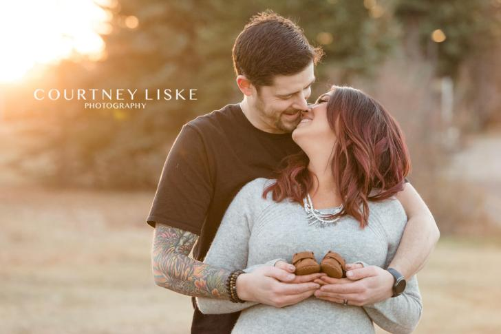 Couple kiss at sunset while holding brown baby shoes