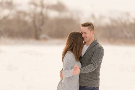 Man and woman dance in open field of snow