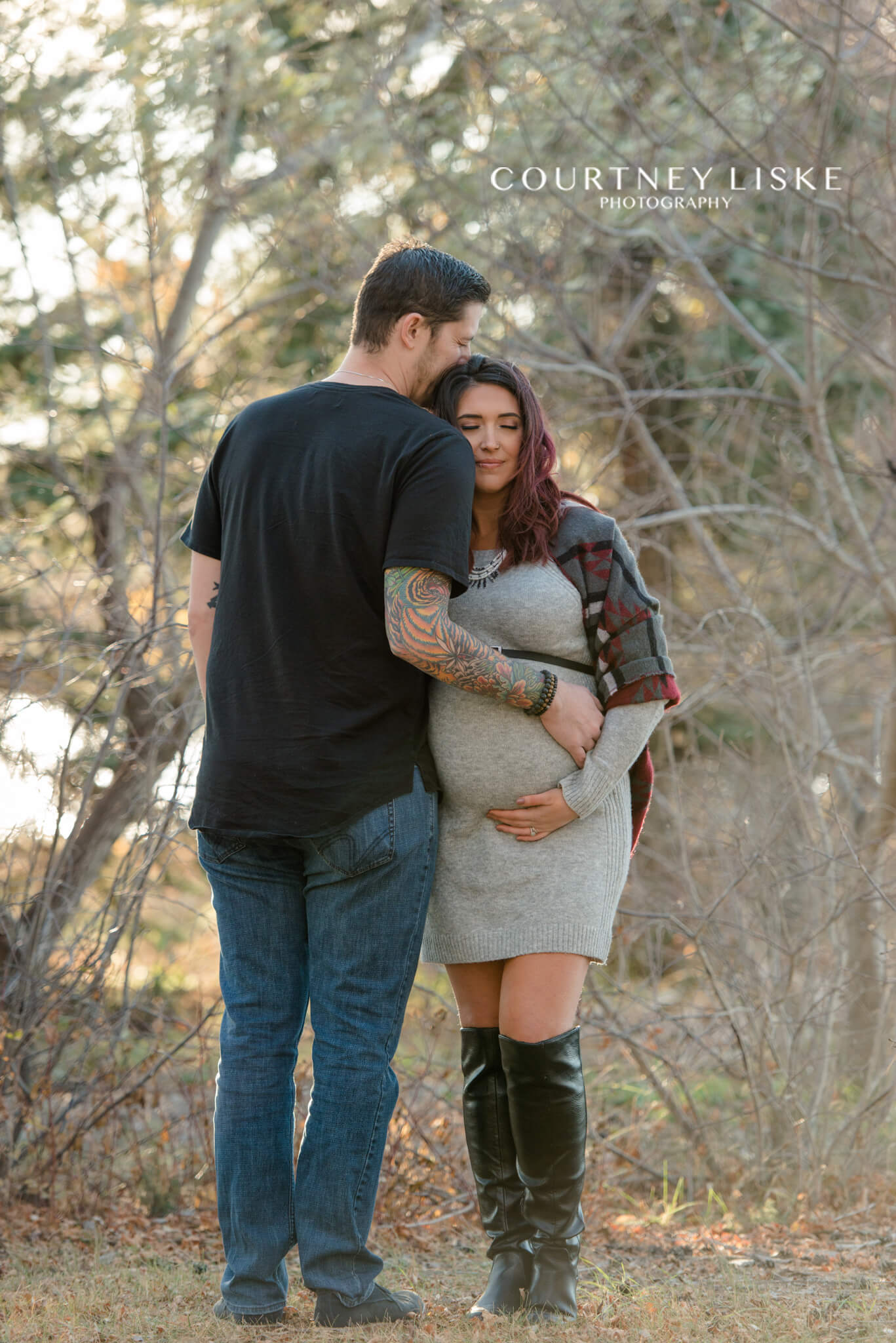 Man in black shirt with tattoo sleeve and pregnant wife