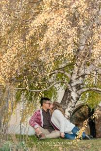 Man in white and red striped sweater kisses fiance under willow tree
