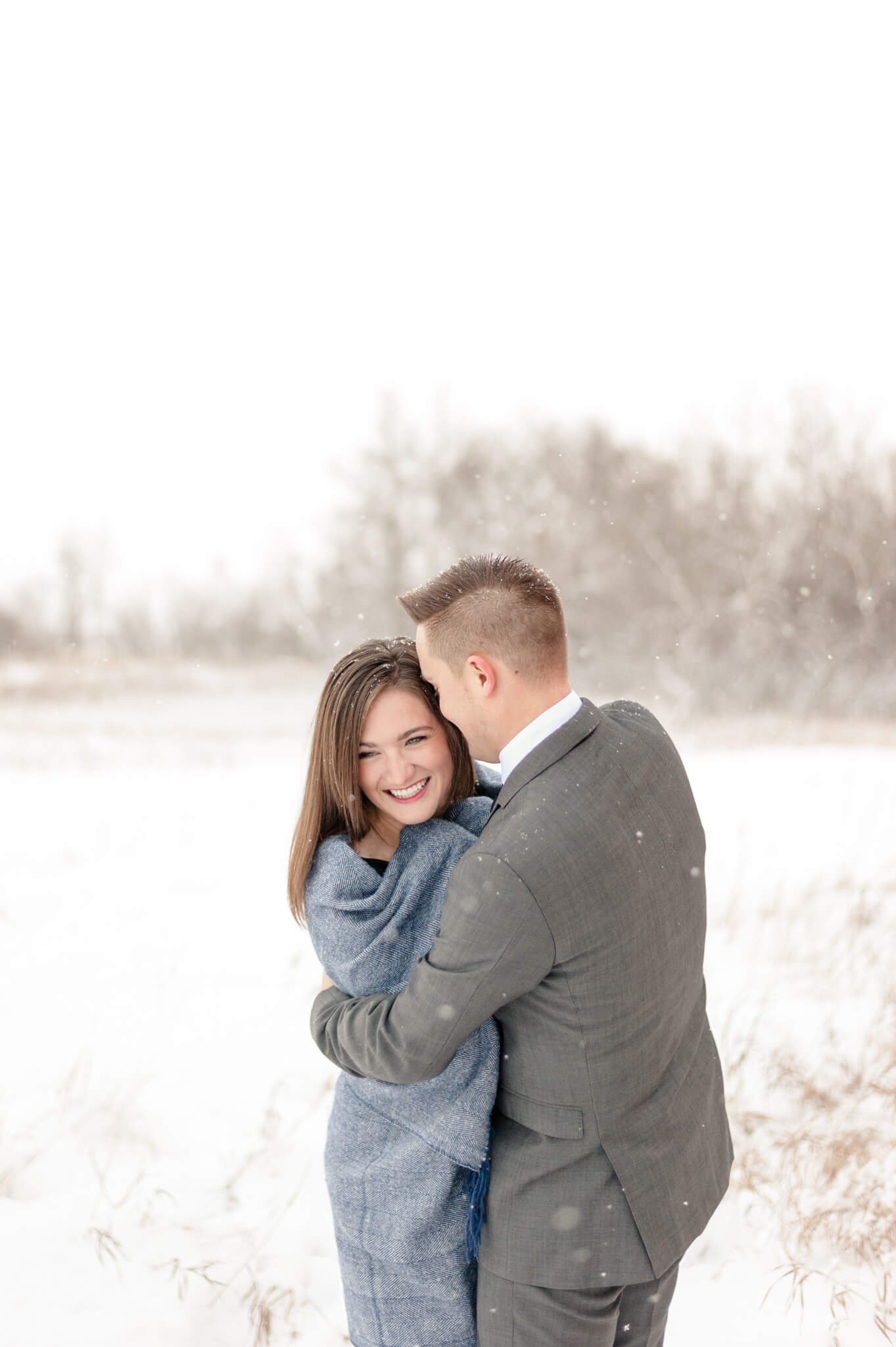 Woman wrapped in blue blanket with her fiancee in grey suit in the snow