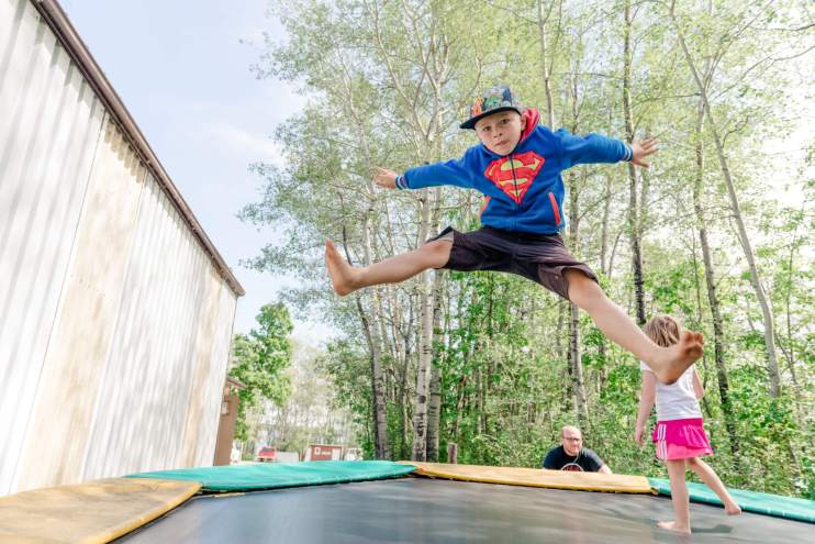 Boy in Superman sweater jumps on a trampoline