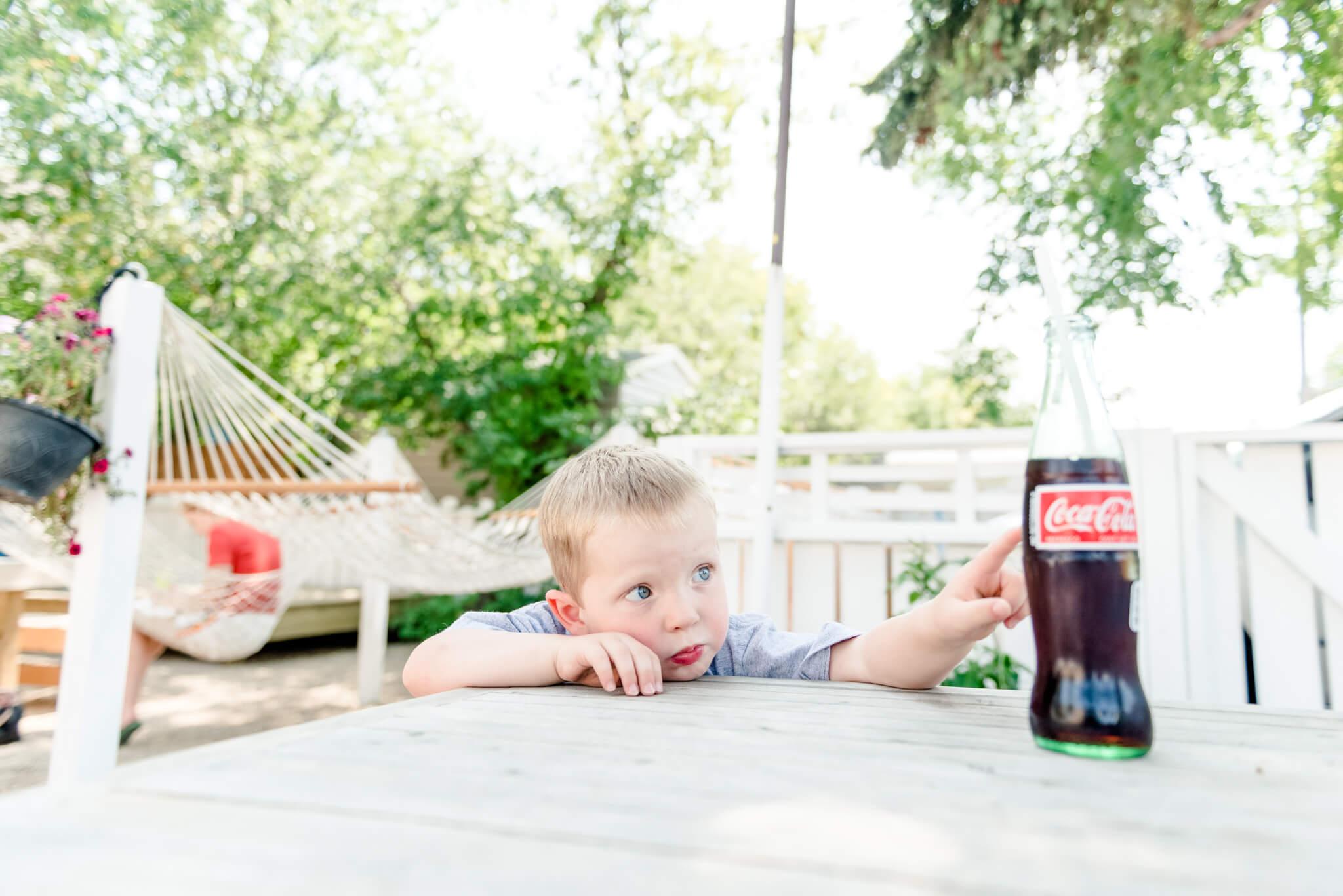 Little boy drinking glass bottle Coca-Cola