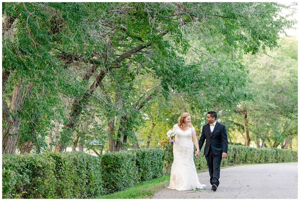 Regina Wedding Photography - Nishant - Corrina - Bridal Portraits - Regina Kiwanis Park - First Look - Bride & Groom walking down path holding hands