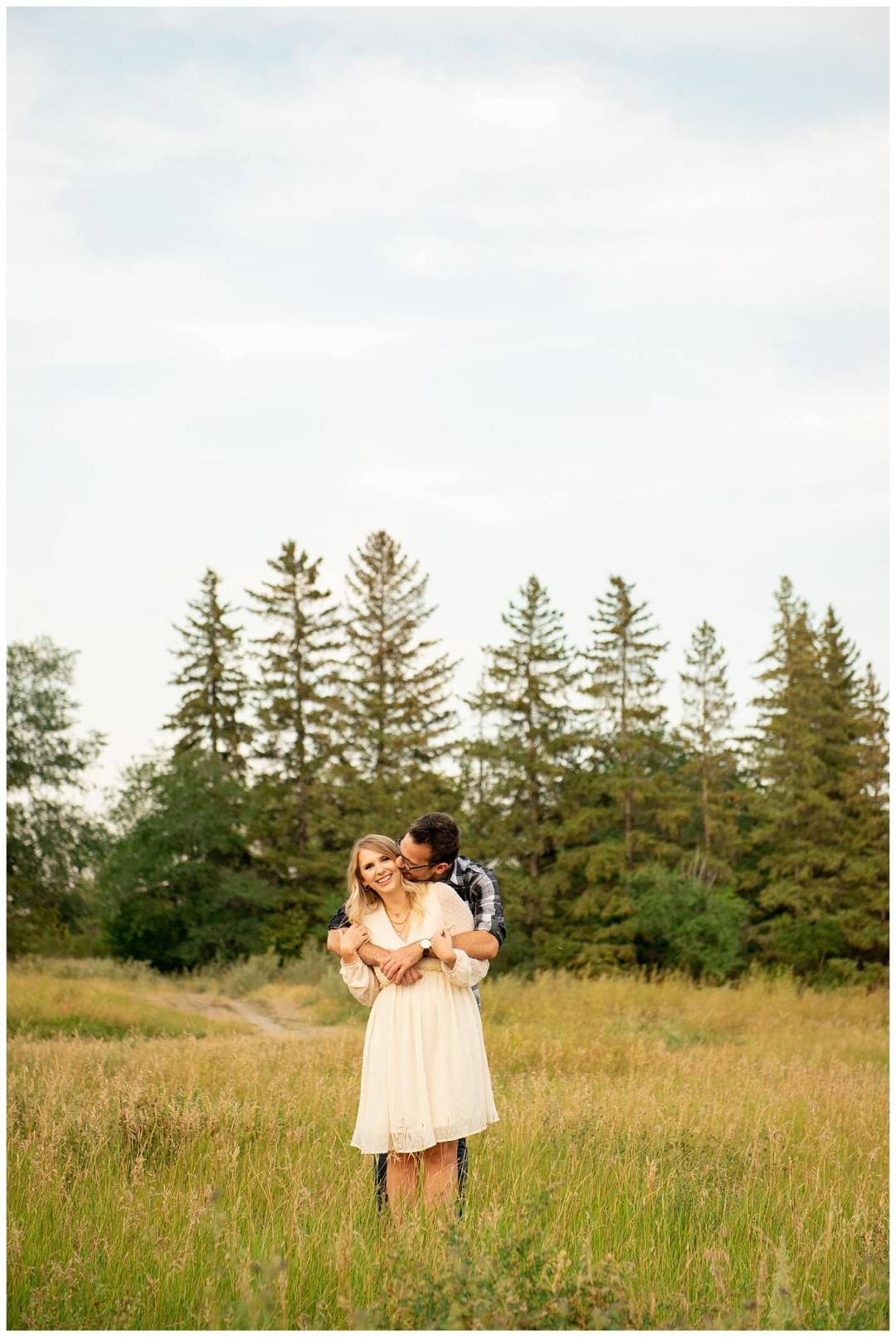 Regina Engagement Photography with Brett & Rachelle. Natural Light Engagement Session in Douglas Park. Regina Couple snuggle in a field of tall grass outside the Wascana Habitat Conservation Area