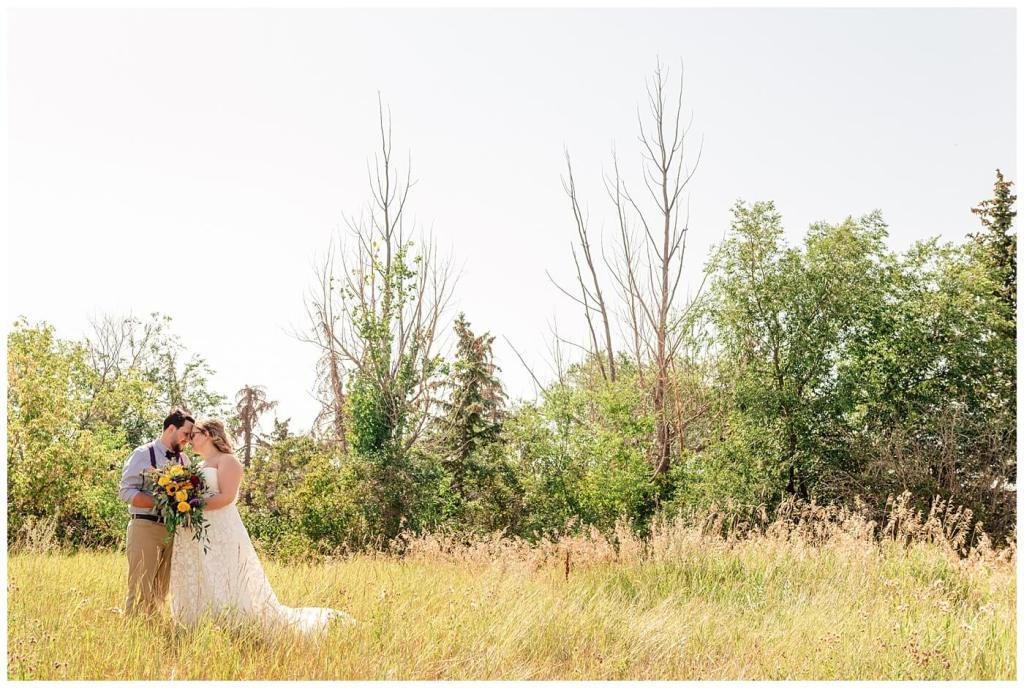Regina Wedding Photographers - Ryan - Aeliesha - Bride & Groom in open field in Regina Park