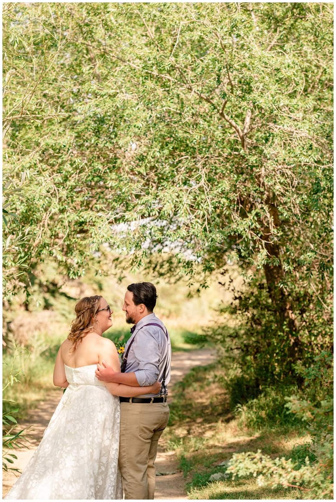 Regina Wedding Photography - Ryan - Aeliesha - Bride & Groom stand under an archway of trees on the island in AE Wilson Park.jpg