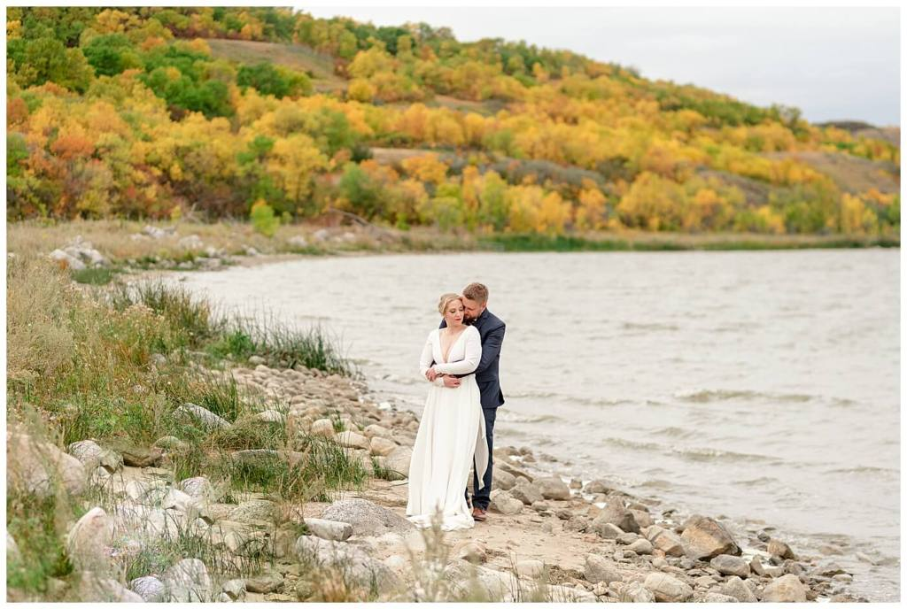 Regina Wedding Photography - Tyrel - Allison - Bride & Groom beside the water among the fall colours of the valley