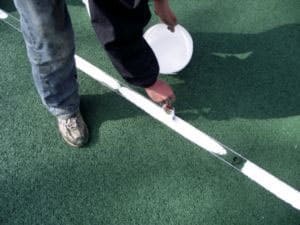 Step 6 or tennis court repair finishing the line using traditional methods.