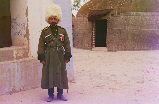 Soldier in tall white fur hat and dressed in old fashioned dark green uniform, standing in front of a house and a yurt.
