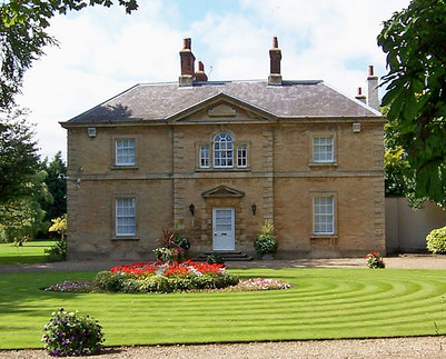 Two-storey country estate house in Great Britain with manicured green lawn and flower bed in foreground.