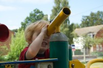 Boy looking through toy telescope