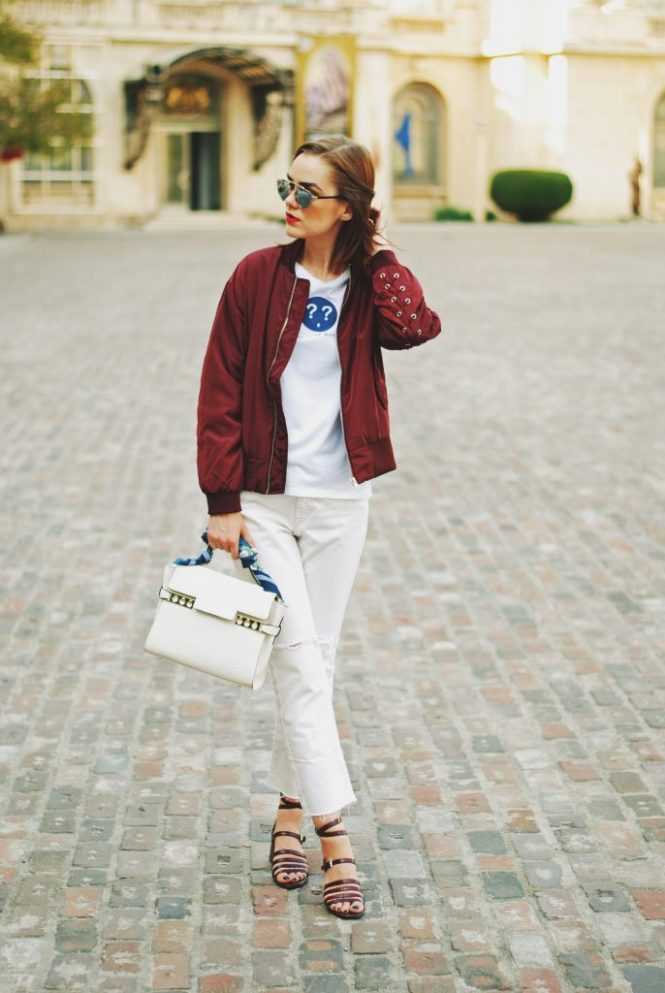 Lace up burgundy bomber jacket, white jeans, strappy sandals, white crossbody bag, sunglasses, fall outfit idea, Andreea Birsan