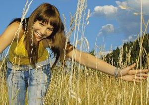 girl in high grass on a sunny day.