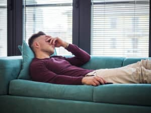 A man lying on the couch and contending with early signs of liver damage from drinking.
