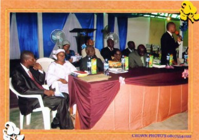 The chairman for the occassion addressing the graduates while other look on