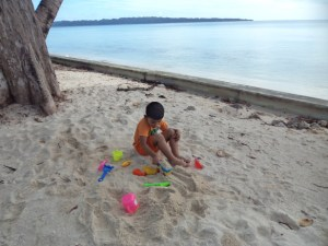 Kiddo enjoying with beach toys during high tide