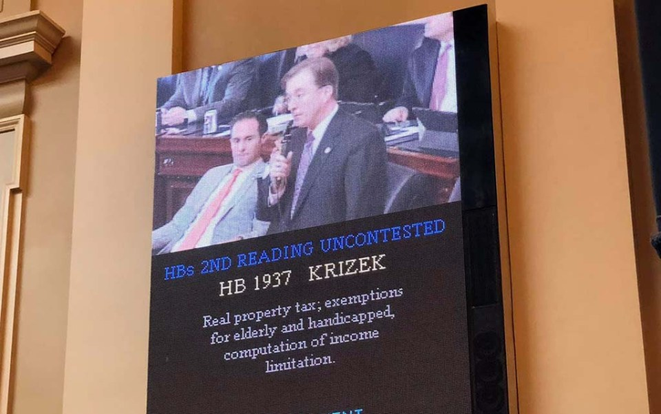 Krizek speaking on the board with text below the screen