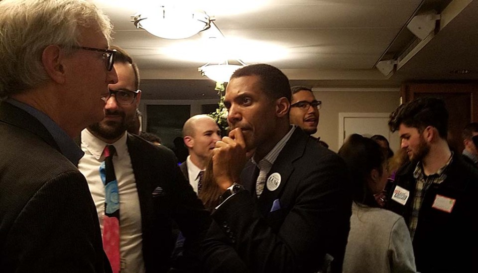Rodney Lusk talking with two men