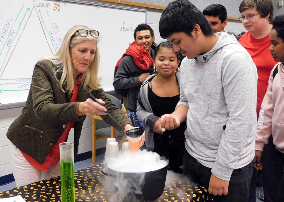 White ladling liquid from a pot as students watch her during a class session.