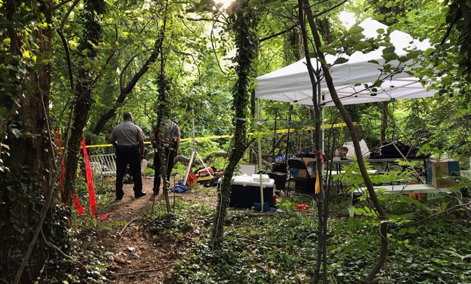 Two officers standing near a tent in the woods