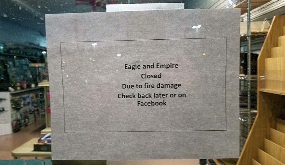 "A piece of paper taped to a window reading ""Eagle and Empire Closed Due to fire damage Check back later or on Facebook"""