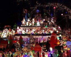 House with lots of Christmas lights and decorations, including inflatables and Santa lights mounted on roof