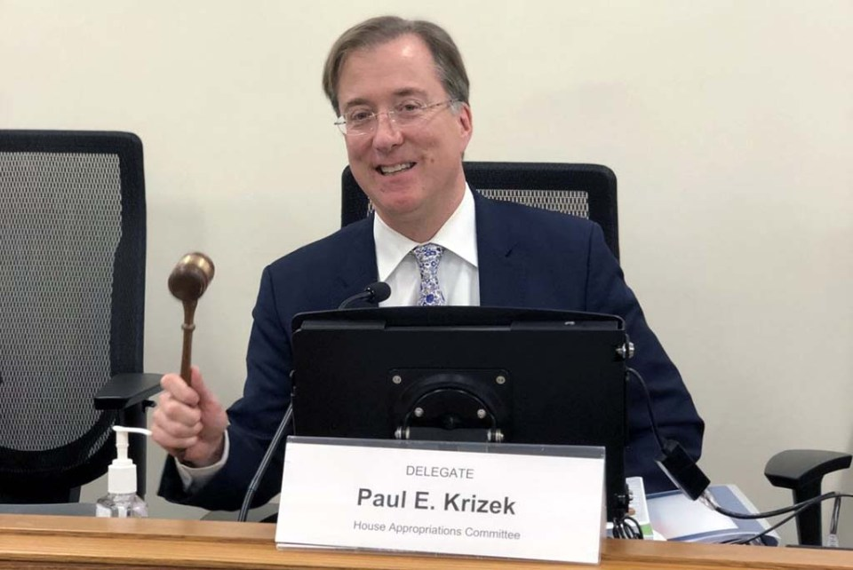 Del. Paul Krizek holding gavel in front of placard with his name on it