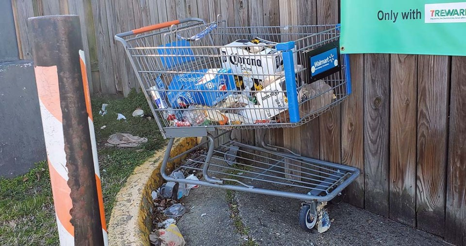 Shopping cart with garbage in it sitting in front of a fence