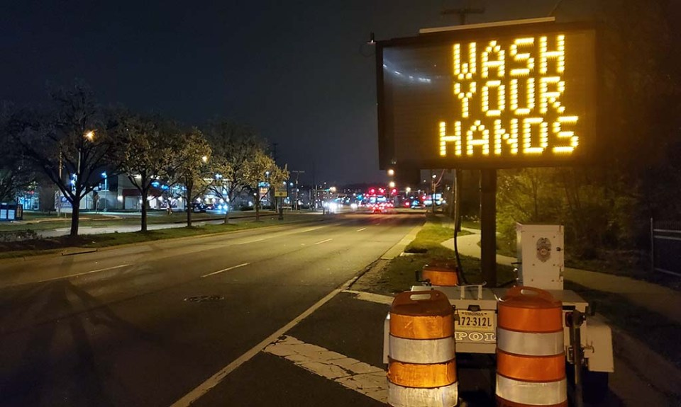"""A """"Wash Your Hands"""" electronic billboard on the side of the road"""