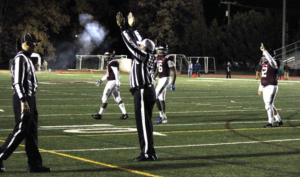 Referee giving the touchdown signal, smoke from cannon in background