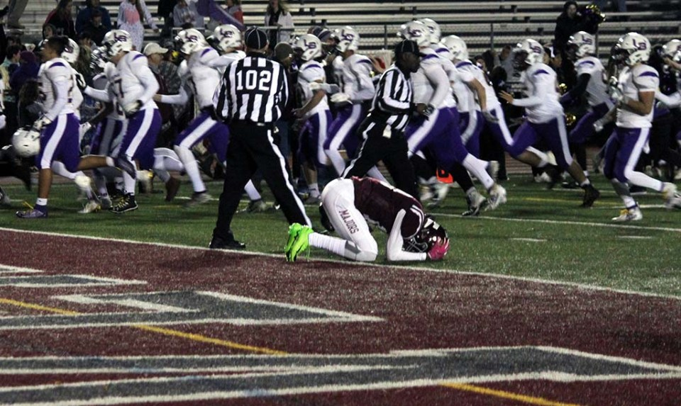 Lake Braddock players running by a Mount Vernon player with his head down