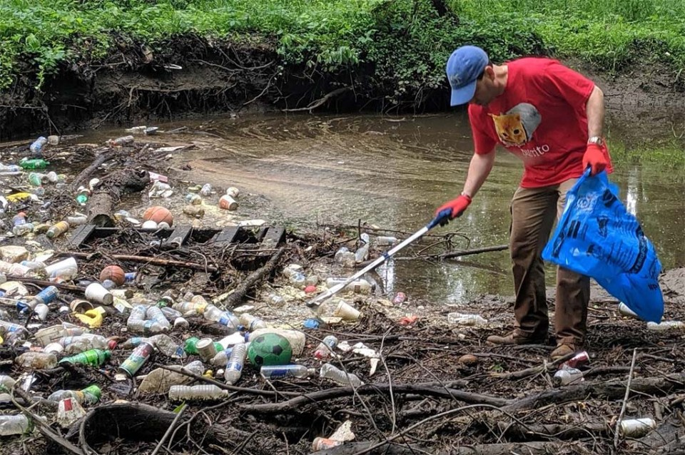 Person pulling trash from large pile in creek